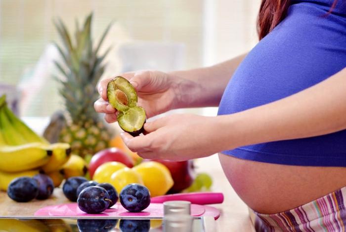 Беременная женщина собирается есть сливы